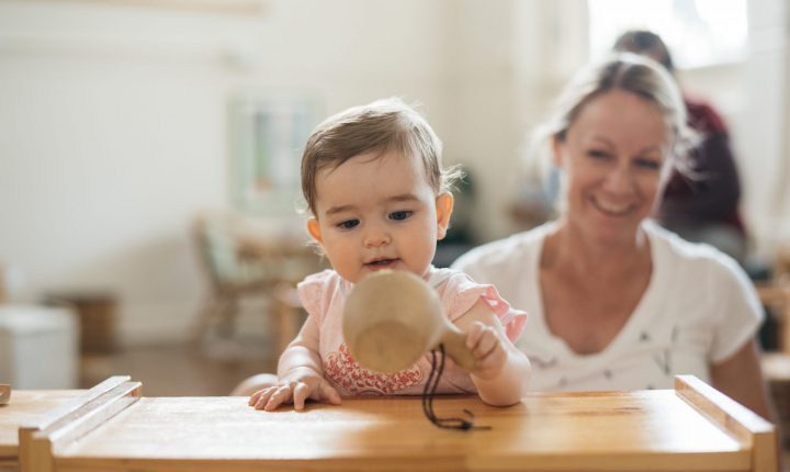Infant exploring wooden cup