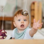 Infant grasping a hanging bell