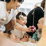 Infants sharing hanging ball