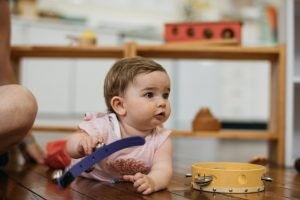 Montessori infant girl playing musical bells