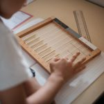 Child calculating on a flat bead frame.