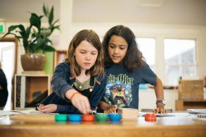Montessori children using square root board and pegs.