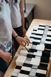 Montessori children playing tone bars.