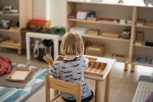 Child using the spindle box mathematics material.
