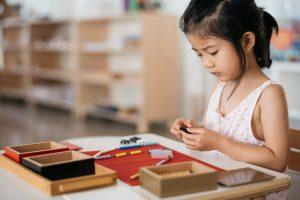 Child using Montessori beads for mathematics work.