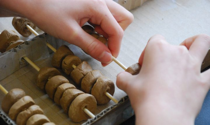 Child making abacus with clay.