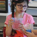 Child conducting an air blocks passage experiment.