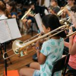 Child playing slide trombone in Montessori band.