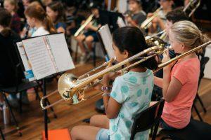 Child playing slide trombone in Montessori band.