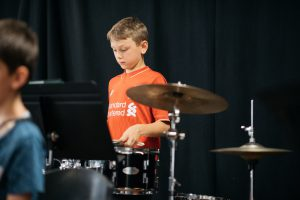 Montessori child playing drums in band.